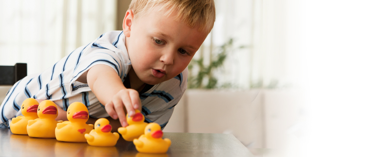 Toddler boy lining rubber duckies in a row based on size