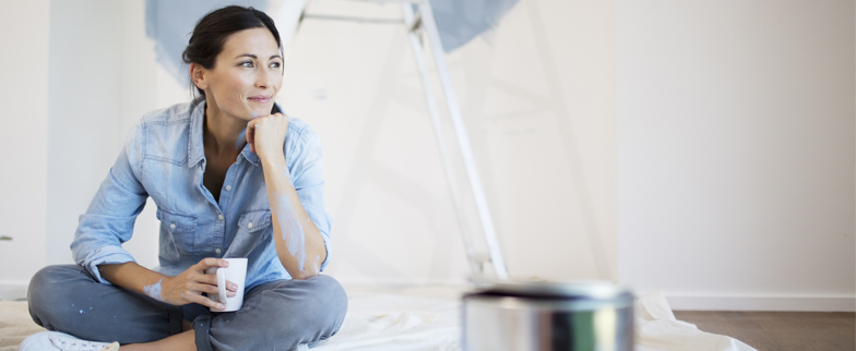 Woman sitting on a floor looking outward, pensively