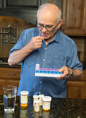 A man holding a selection of pills in one hand, and a 7-day pill box in the other.