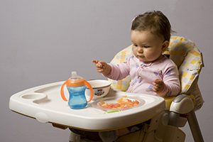 Baby sitting in high chair with sippy cup, reaching for finger foods.