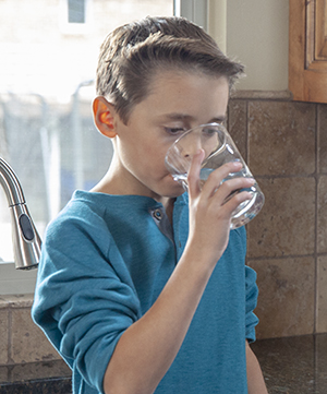 Boy drinking a glass of water.