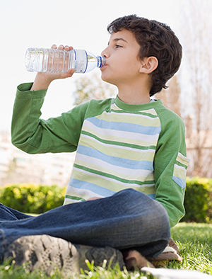 Boy drinking water from water bottle.