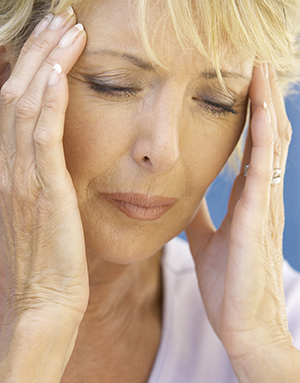 Woman with headache pressing her temples.