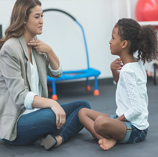 Child sitting with a speech therapist.