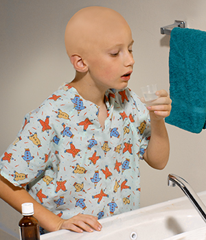 Child standing at bathroom sink preparing to rinse mouth. Bottle of rinse is on counter next to sink.