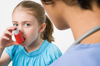 Child using an inhaler with nurse nearby