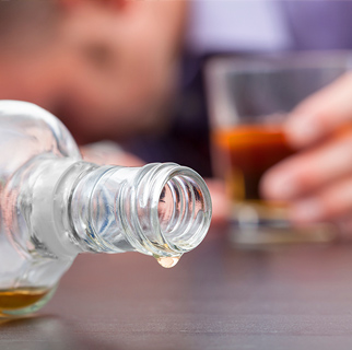 close up image of a spilled bottle of whisky, a glass with a hand on it and a mans face, face down on a table.