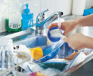 Manos con guantes de goma en el fregadero de la cocina, lavando un plato con agua y jabón.
