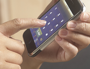 Closeup of hands holding cell phone.