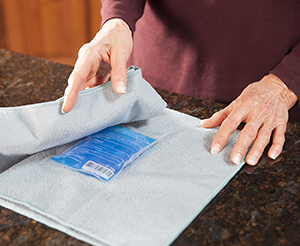 Closeup of hands wrapping ice pack in thin towel.