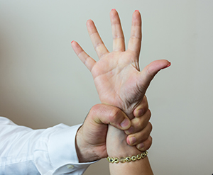 Closeup of male hand firmly holding a female wrist.