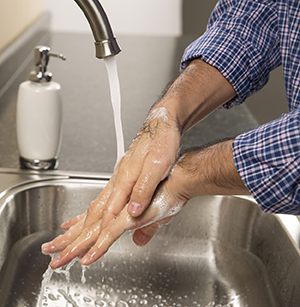 Closeup of man washing hands in sink.