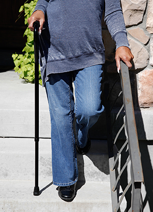 Closeup of woman holding handrail and using a cane while walking down stairs outdoors.
