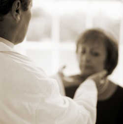 Doctor checking woman for swollen glands in the neck
