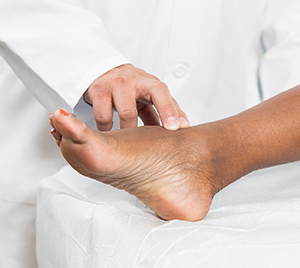 Doctor examining woman's foot.