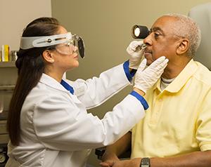 Doctor examining man's nose.
