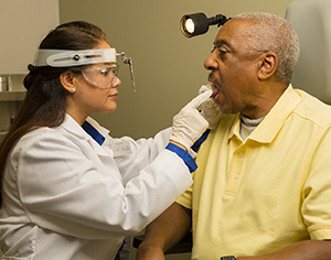Doctor examining patient's mouth.