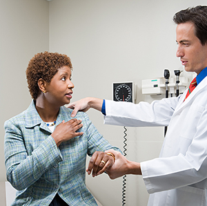 Doctor examining woman's shoulder.
