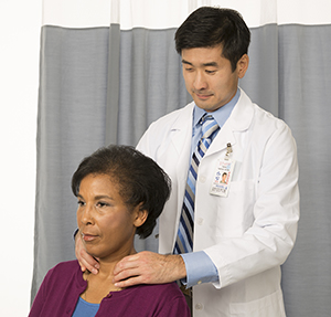Doctor feeling woman's neck to examine thyroid.