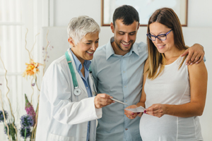 Doctor having conversation with pregnant couple.