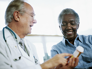 Doctor holding a prescription bottle and discussing prescription with patient.