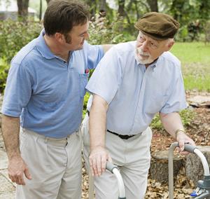 Elderly man helped by male caregiver.