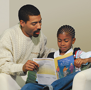 Man reading booklet with boy.