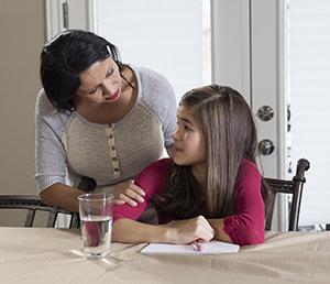 Girl doing homework, talking to mom.