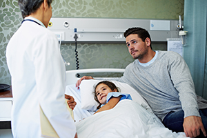 Girl in a hospital bed with her father talking to a doctor.