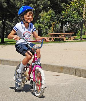 girl riding bike wearing helmet