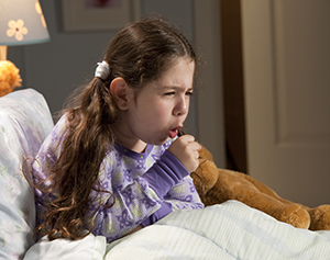 Girl sitting up in bed, coughing.