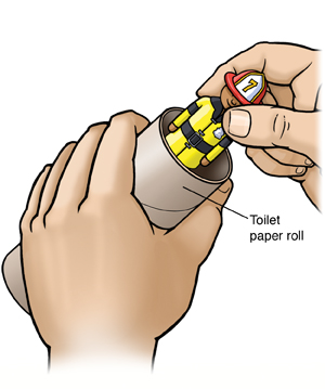 Hand holding toilet paper roll. Another hand inserting small toy into roll.