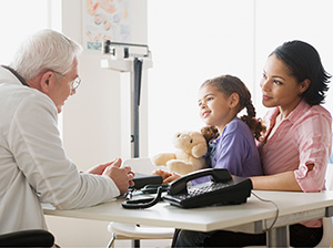 Healthcare provider talking with a girl and her mother.