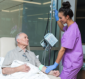 Healthcare provider caring for man having infusion treatment.