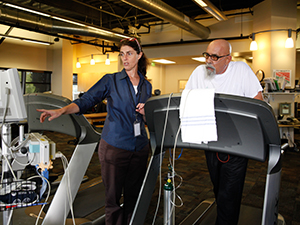 Healthcare provider coaching man walking on treadmill wearing nasal cannula.