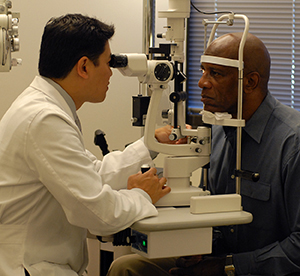 Healthcare provider examining man's eyes.