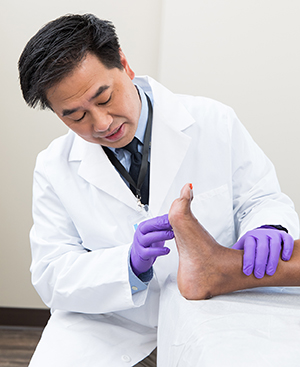 Healthcare provider examining man's foot.