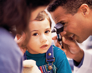 Healthcare provider examining toddler's ear with otoscope.