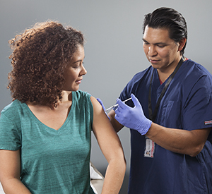 Healthcare provider giving injection in woman's arm.