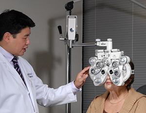 Healthcare provider giving woman eye exam.