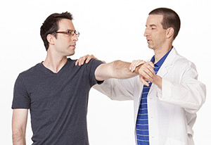 Healthcare provider helping man do shoulder exercise.
