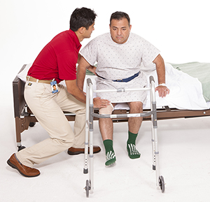 Healthcare provider helping man stand up from hospital bed with walker nearby.