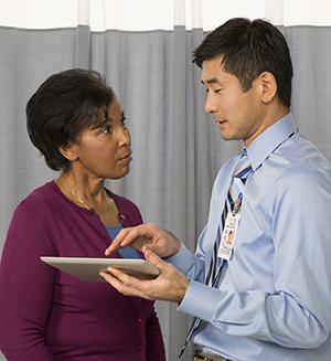 Healthcare provider holding electronic tablet, talking to woman.