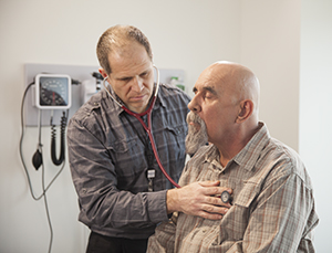 Healthcare provider listening to man's chest with stethoscope.