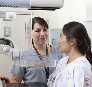 Healthcare provider positioning woman for mammogram.