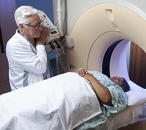Healthcare provider preparing woman for CT scan.