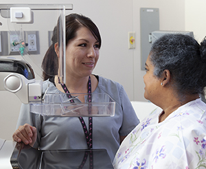 Healthcare provider preparing woman for mammogram.