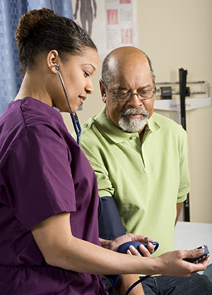 Healthcare provider taking man's blood pressure.
