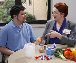Healthcare provider talking to man. Measuring cups and spoons, fruits and vegetables are on table.