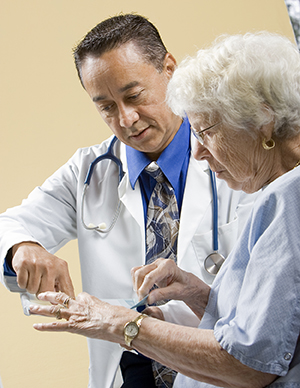 Healthcare provider talking to patient in exam room.